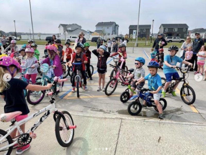 Kids on bikes in a school parking lot