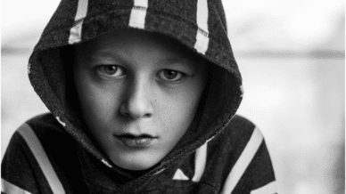 young boy wearing a hooded sweatshirt looks sad