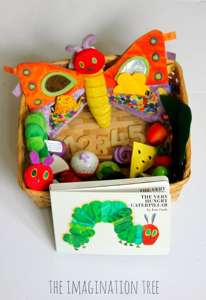 A basket filled with a plush caterpillar and items of toy food with the book The Very Hungry Caterpillar in front