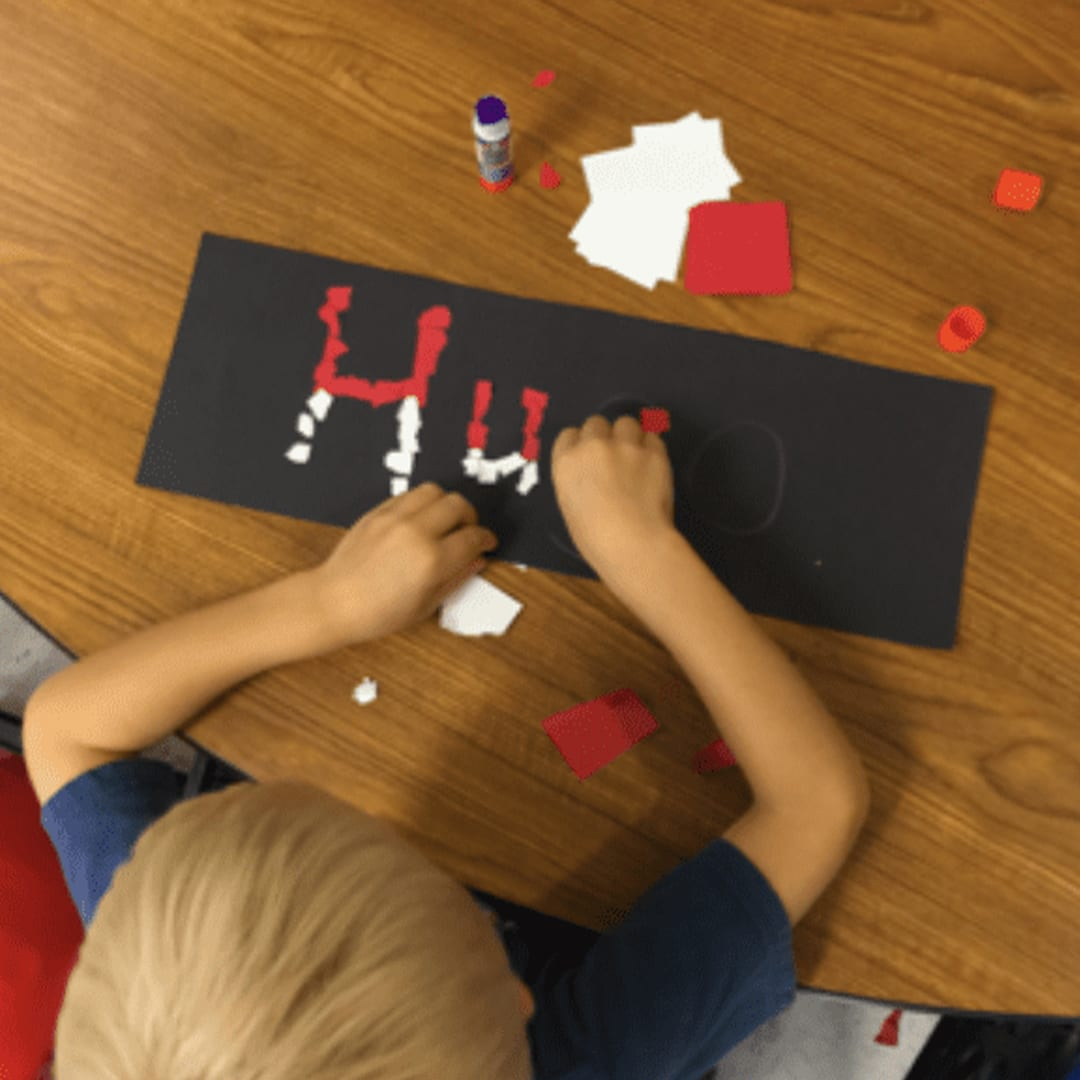 A student sitting at a desk making letters out of shapes inspired by Pokemon having the best day ever at school.