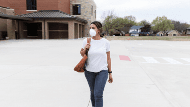 A young teacher wearing her N95 mask will walking on an empty school campus.