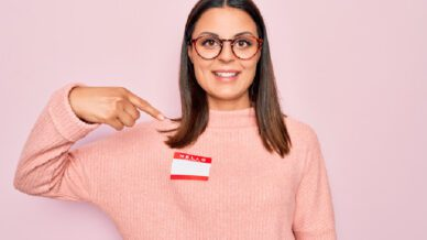Young woman pointing to nametag on pink sweater 5 Alternative Teacher Names to Try in Your Classroom This Year
