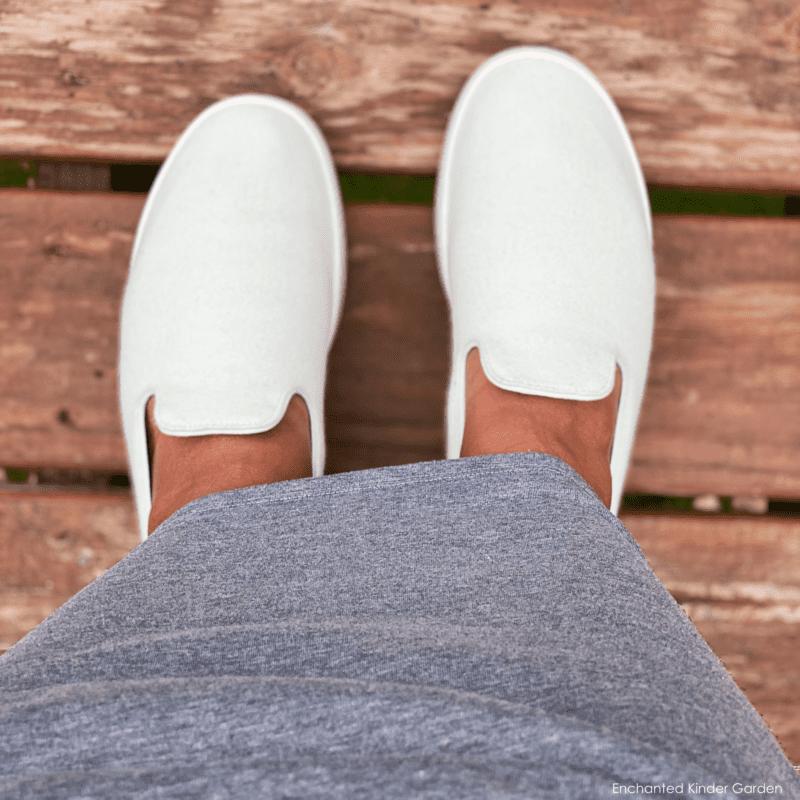 Woman's legs wearing long gray skirt and light green Allbirds Wool Loungers