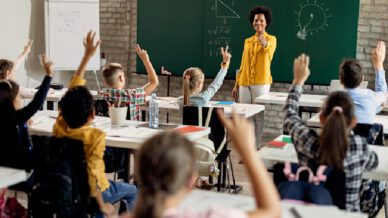Happy African American teacher in front of a class and gesturing at her students who are raising their hands to answer the question in the classroom.