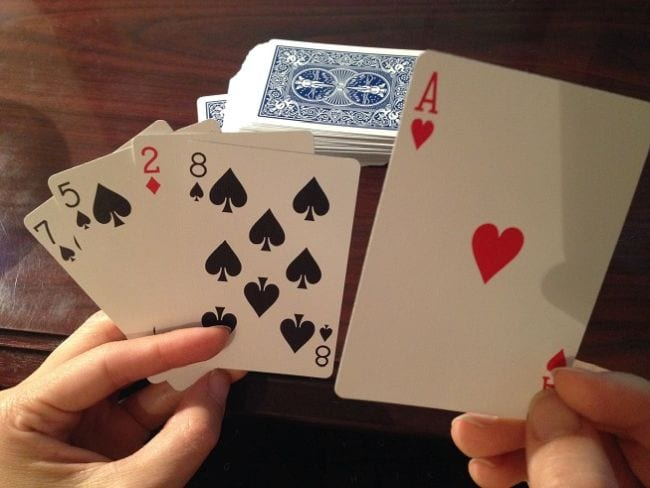 Hands holding playing cards in front of a stack of cards
