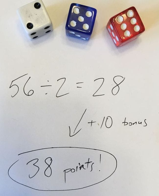 Three dice next to division problem 56 / 2 = 28 + 10 bonus is 38 points!