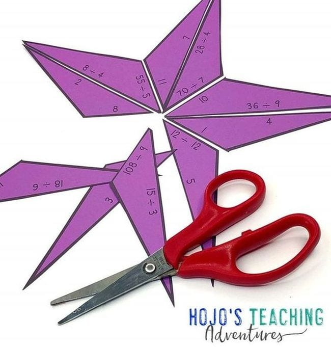 Paper star with division problems and answers, cut into pieces with pair of scissors