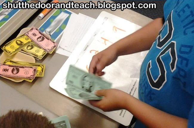 Student counting play money into piles