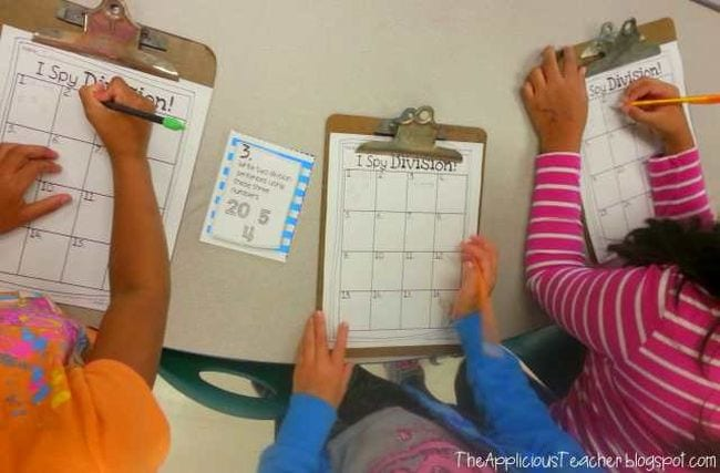 Students using pencils to write on I Spy Division worksheets on clipboards (Teaching Division)
