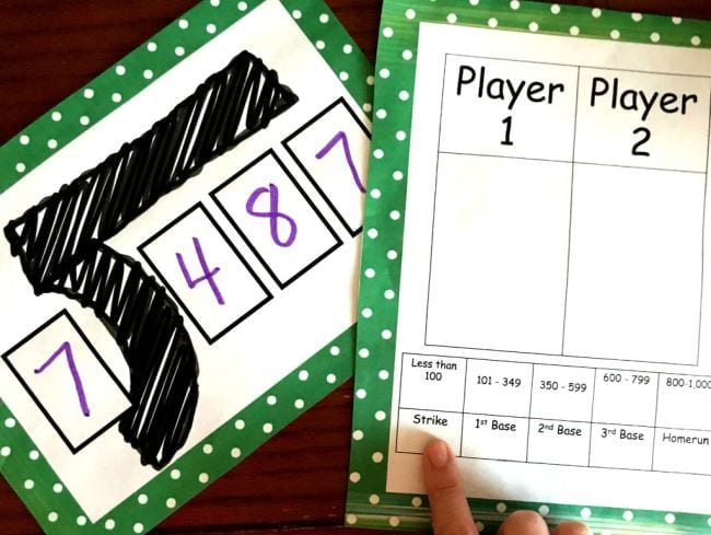 Card showing division problem 487 divided by 7 with game worksheet