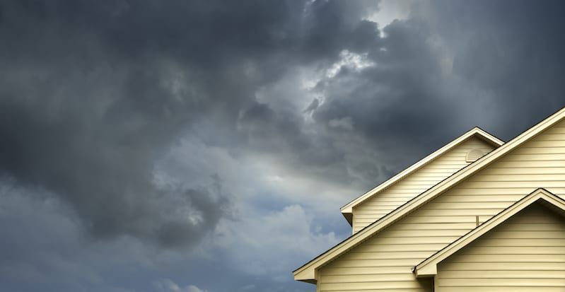A picture of a house with a stormy sky above it.