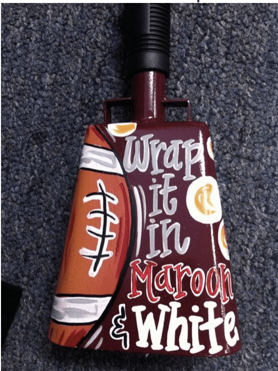A brown cowbell with a school spirit message written on it.