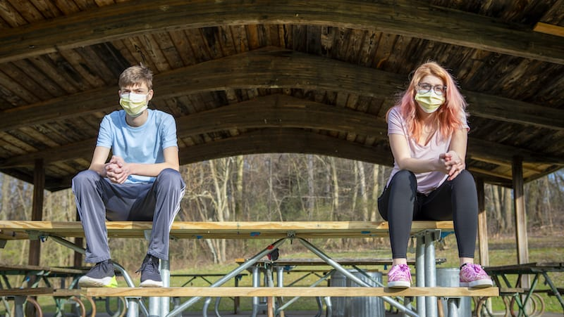 Teenage siblings wearing face masks sitting at a park grove outdoors with their face masks on keeping a social distance during the coronavirus pandemic.