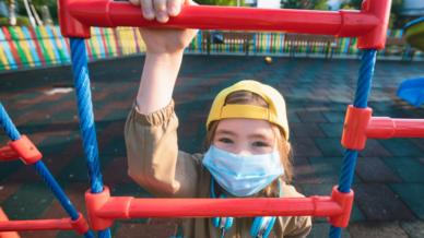 Girl in mask climbing ladder