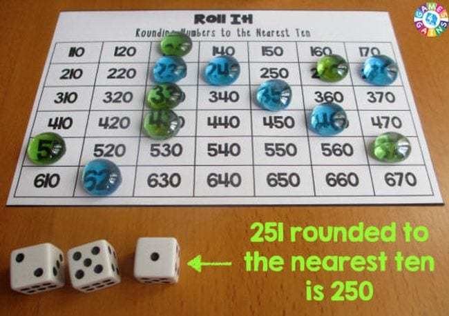 Roll It rounding game with markers and dice showing 2, 5, and 1. Text reads 251 rounded to the nearest ten is 250.