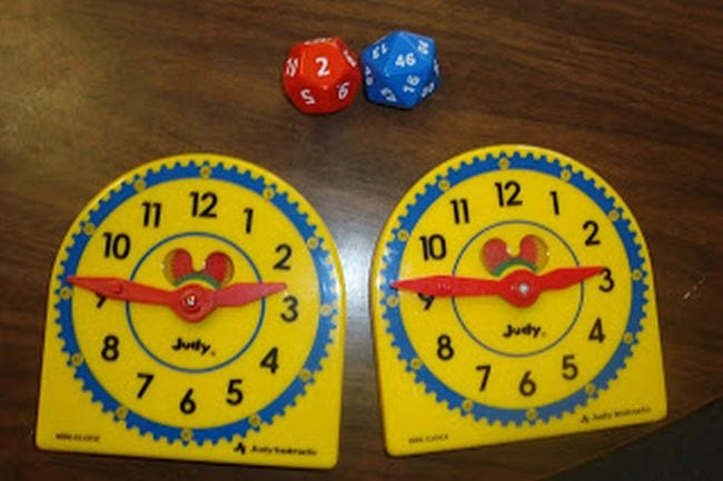 Two toy clocks next to a pair of polyhedral dice