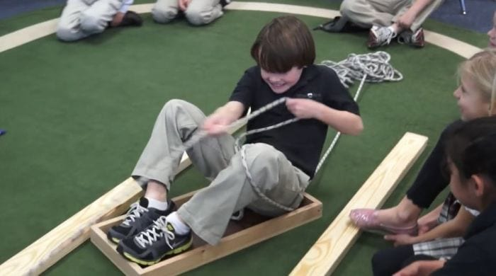 Third grade science student sitting in a wood tray, pulling himself along with a rope