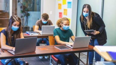 Female high school teacher offering assignment assistance and three students in classroom setting wearing face masks and working at desks observing social distancing using technology of laptop computers and digital table.