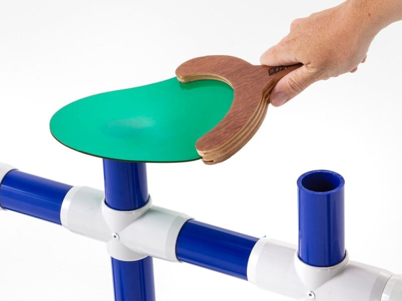 a student hits a hollow plastic tube with a paddle to test for sound waves