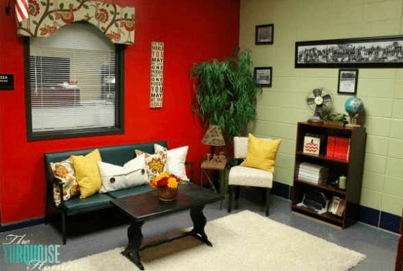 principal's office with red wall, colorful window valance and cozy seating area