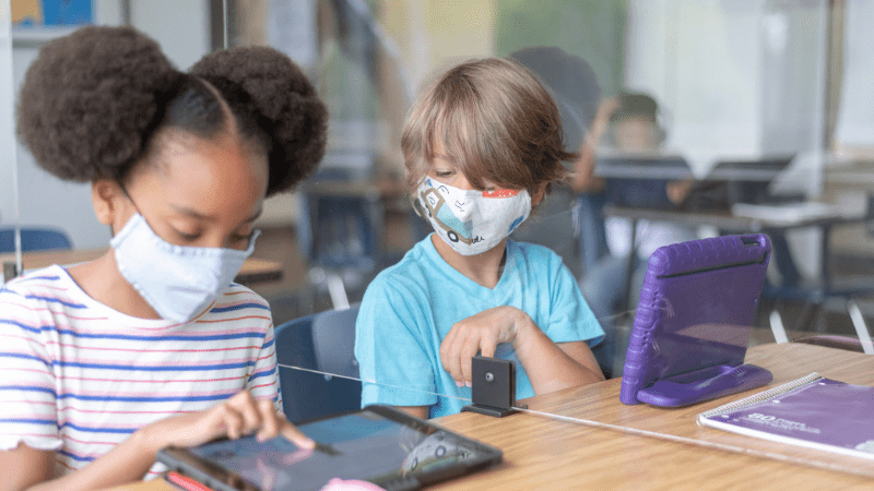 Two masked students working on iPads
