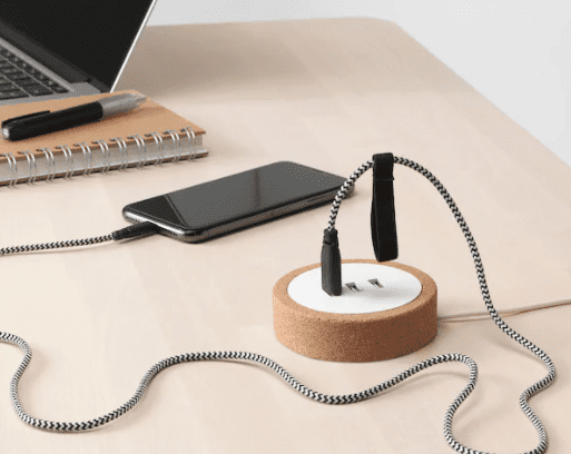 desktop USB charger on a desk with a phone connected to it