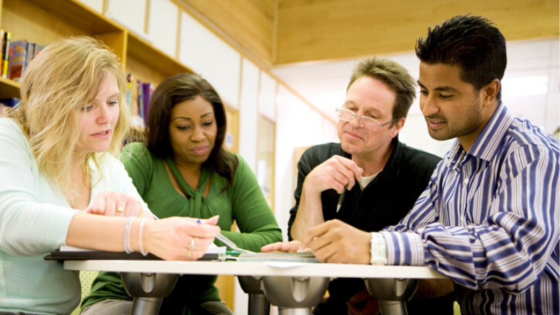A group of adults sitting by a circle desk looking at a piece of information.