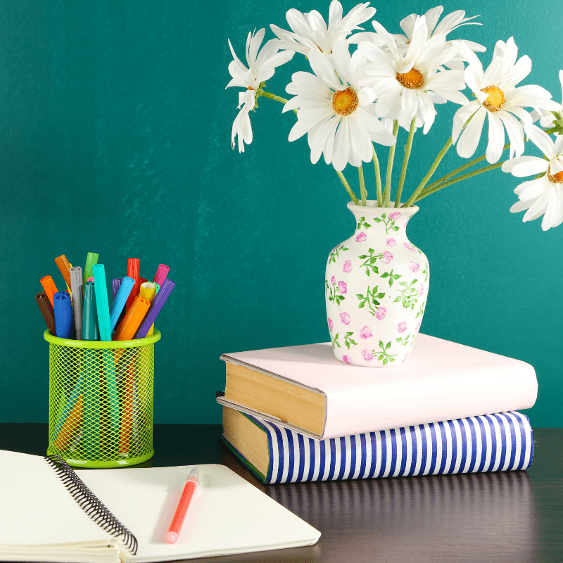 Flowers in a vase sitting on a desk with books and pens
