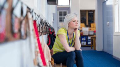 stressed teacher sitting on bench outside classroom - teacher stress