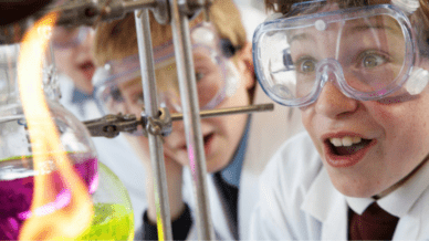 Excited students in lab coats and goggles looking at flame—STEM Activities for Middle School