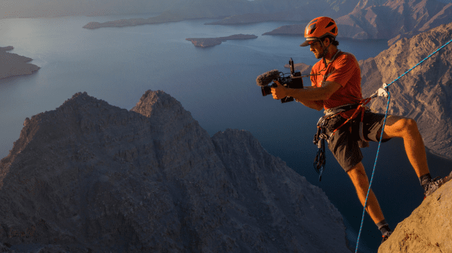 National Geographic Explorer rock climbing with a video camera