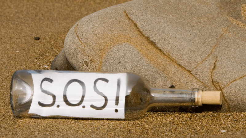 Glass bottle on the beach with S.O.S. written on a paper inside the bottle