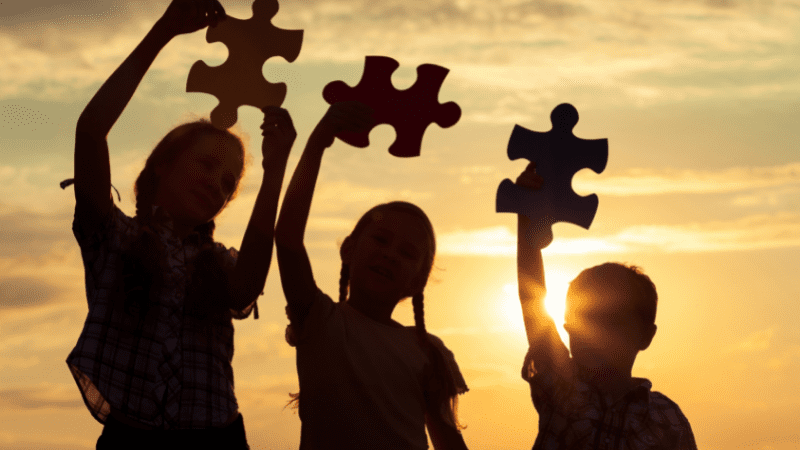 Three students in silhouette holding up large puzzle pieces