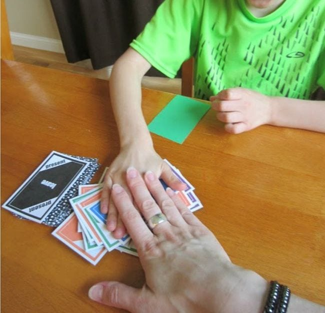 Student and adult slapping their hands on a pile of colorful cards (Verb Tenses)