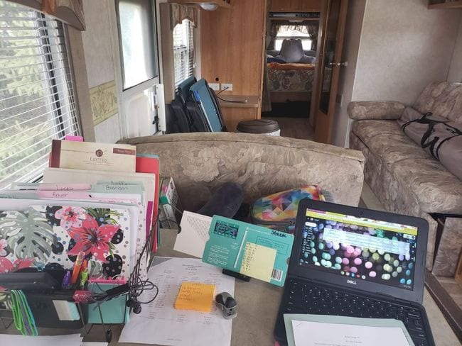 Interior of an RV with a desk set up for mobile teaching including a laptop, folders, and EZGrader