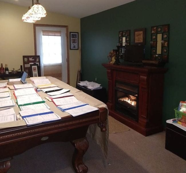 Pool table at teacher's home covered with file folders for remote learning