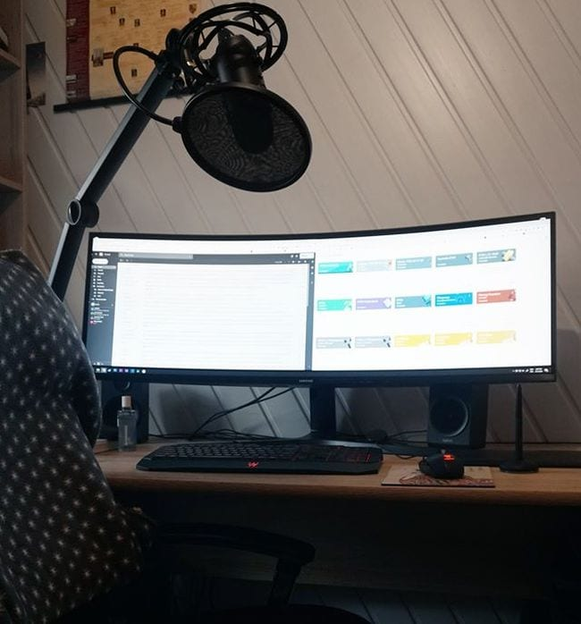 Curved screen and computer on desk with overhead microphone and light