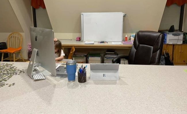 Apple computer on desk with computer chair and small child in background