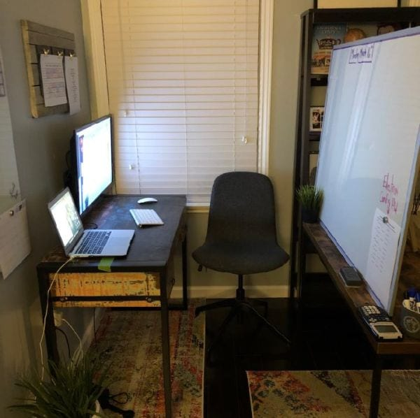 Virtual classroom with whiteboard, desk, laptop and computer screen in living room