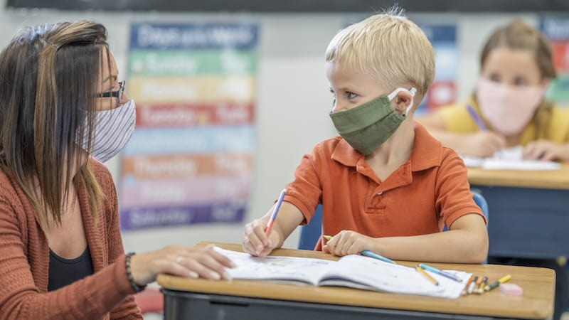 School teacher assisting student in classroom while both wearing masks to protect from the transfer of germs.
