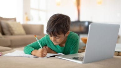 A young boy using laptop while drawing a sketch on book at home.