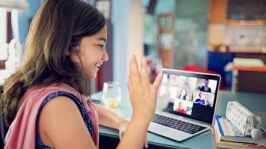 Schoolgirl is e-learning and video conferencing at home.