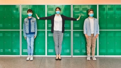 Teenage boys and female teacher wearing N95 face masks standing in front of school lockers. Woman outstretching arms in the distance.