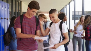Happy teenage boys sharing exam results in school corridor.