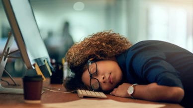 An exhausted young businesswoman sleeping at her desk during a late night at work.