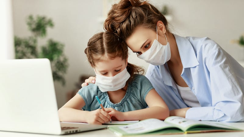 Exhausted woman in medical mask sitting at table and watching diligent girl writing in notebook while doing homework together during pandemic.