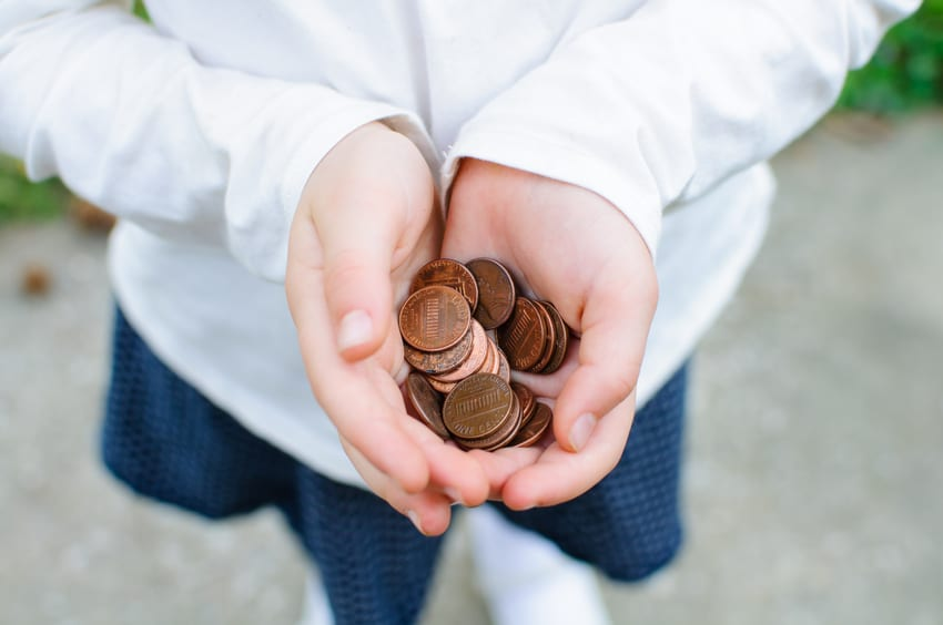 A handful of pennies rest in a girl's cupped hands.