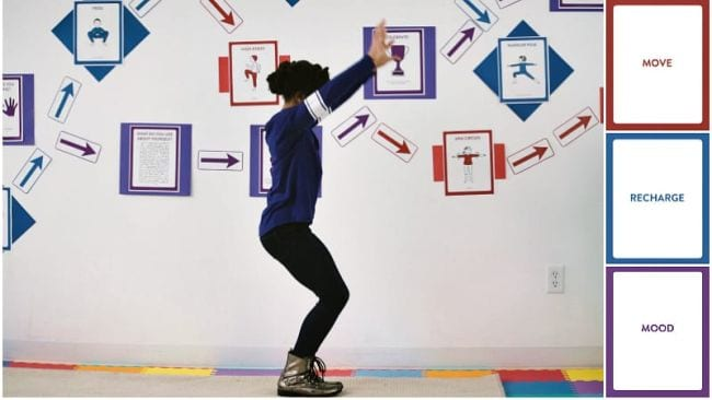 Child doing a yoga pose in front of a school wall with various movement posters