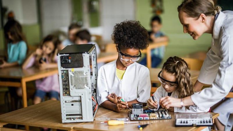 A STEM teacher teaching two young kids about programming the inside of a desktop computer.