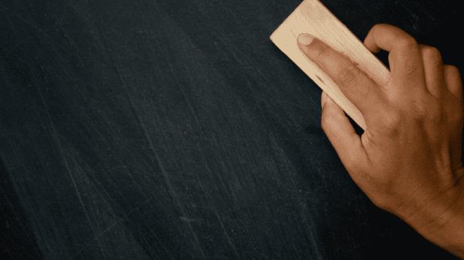 Black hand wiping slate clean